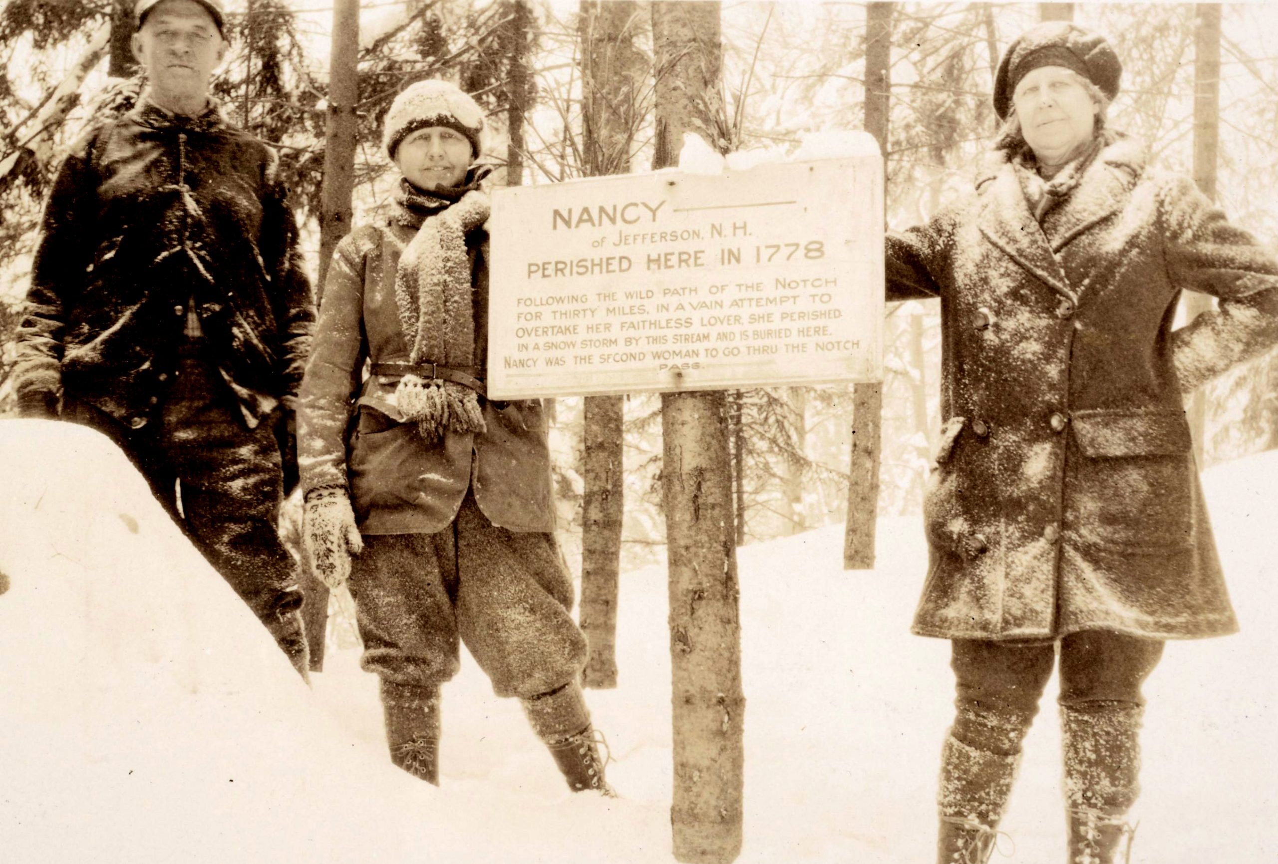 Some hikers stand near a sign marking where Nancy Barton is buried.